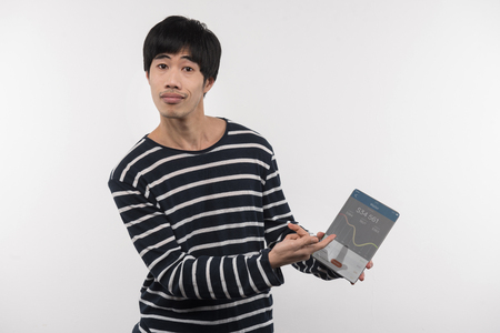 Stock market. Nice Asian man pointing at the tablet screen while working with a stock market Banco de Imagens