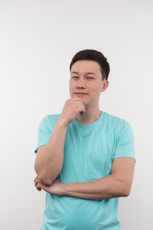 Creative solution. Pleasant thoughtful man holding his chin while having a smart creative idea Stock Photo