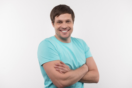 Being happy. Positive delighted man standing with his arms crossed while smiling to you Stock Photo