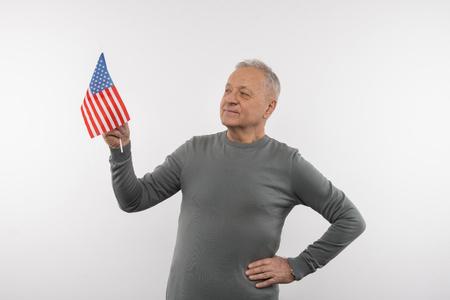 My nationality. Joyful senior man smiling while holding the US flag