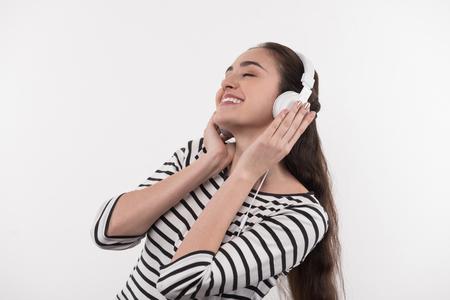 Pleasurable mood. Joyful happy woman smiling while enjoying the music