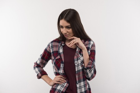 Professional model. Cheerful attractive woman touching her chin while having a photo shoot