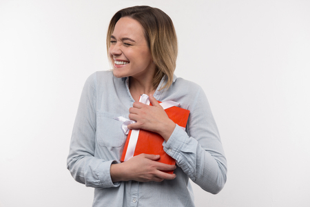 Joyful mood. Delighted nice woman holding the present while being in the joyful mood Banco de Imagens