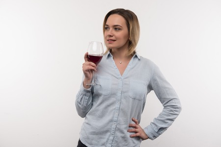 Alcoholic drink. Delighted happy woman smiling while having a glass of wine Banco de Imagens