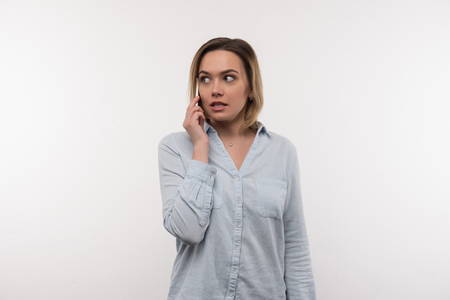 Phone conversation. Pleasant nice woman talking on the phone while standing against white background