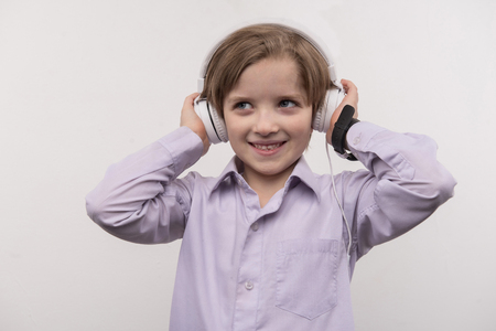Favourite music. Happy cute boy touching his headphones while listening to music Banco de Imagens