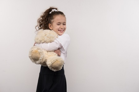 My bear. Happy young girl hugging her toy while standing against white background