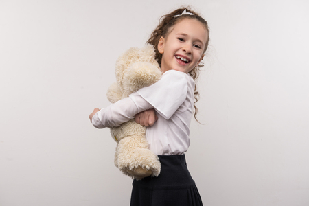 Beautiful toy. Delighted nice girl hugging her bear while feeling happy