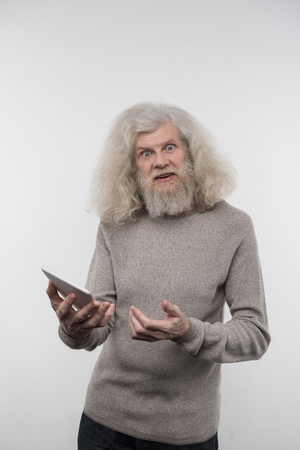 Technological age. Happy aged man feeling happy while using modern technology