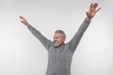 So happy. Joyful emotional man holding his hands up while expressing his happiness Banco de Imagens