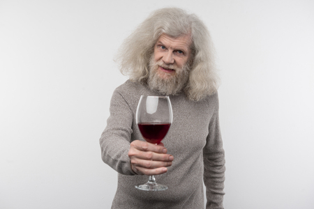 Try it. Positive aged man smiling while offering you wine