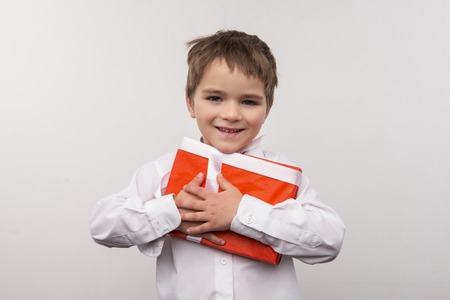 Christmas gifts. Cute small boy hugging a present while being happy about Christmas
