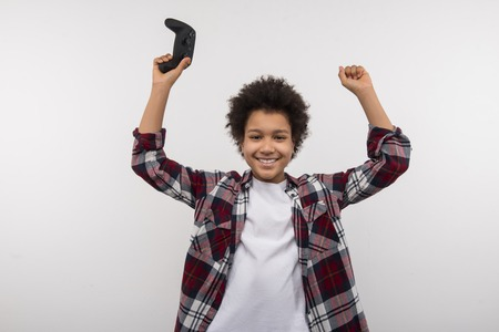Time to relax. Joyful happy boy cheering while holding a video games console