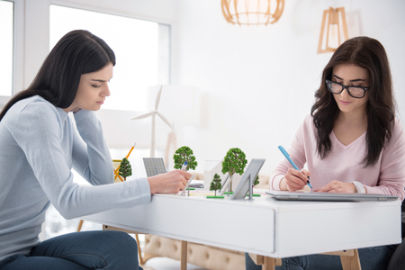 Eco project. Pensive immobile woman and student writing down and helping each other with task Stock Photo