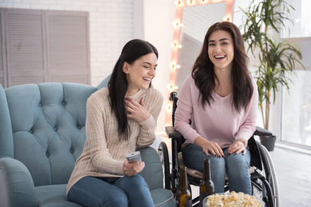 Too much fun. Positive sister and disabled woman watching film and laughing Imagens
