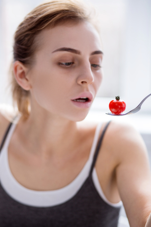 Small meal. Selective focus of a small tomato being eaten by a cheerless young woman