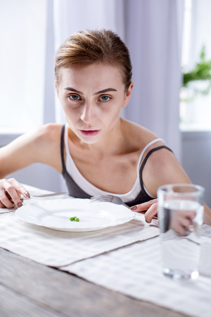 Meal time. Cheerless pale woman sitting at the table while eating her meal