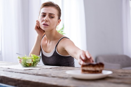 My wish. Depressed young woman wanting a cake while being on a diet Stock Photo