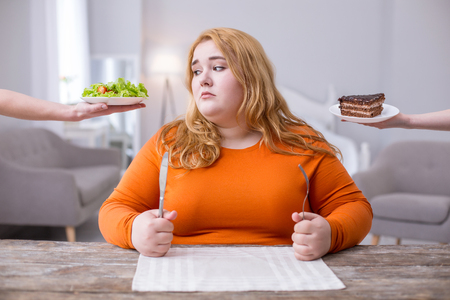 Being fat. Miserable plump woman looking at a salad and wanting cookies Standard-Bild