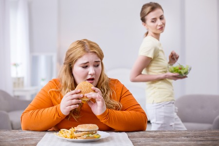 Ser un paria. Miserable mujer corpulenta comiendo un sándwich y su delgada amiga sonriendo burlonamente Foto de archivo - 101053155