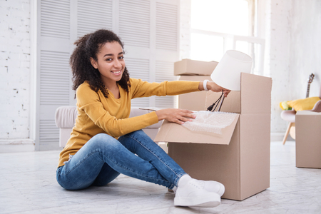 New life milestone. Upbeat curly-haired girl posing for the camera while sitting on the floor and packing a table lamp into the box Stock Photo