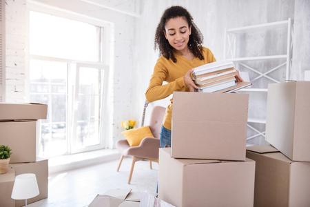 Libros Favoritos. Agradable chica de cabello rizado empacando una pila de libros en una caja grande antes de mudarse de la habitación del dormitorio. Foto de archivo