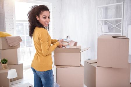 Gute Stimmung. Schönes junges Mädchen, das in die Kamera lächelt, während es ihre Sachen auspackt und einen Stapel Bücher aus der Schachtel nimmt