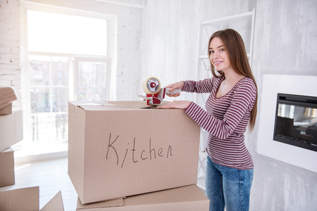 Bye old house. Beautiful dark-haired woman smiling and the camera and posing while closing a box with kitchen utensils
