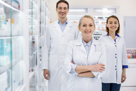 Enthusiastic three pharmacists smiling to camera while staying in drugstore Stock Photo