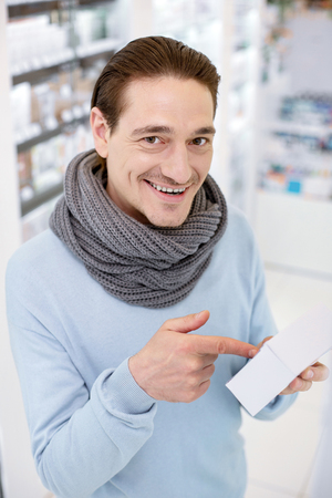 Common cold. Top view of jolly exuberant man wearing scarf while deciding on medication for relieving cold symptoms Stock Photo