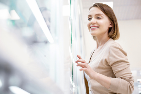 Store services. Low angle of happy glad woman posing in blurred background and grinning Stock Photo