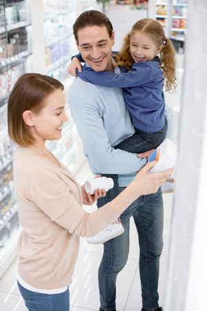 Healthy family. Top view of happy merry woman choosing drug while man holding girl