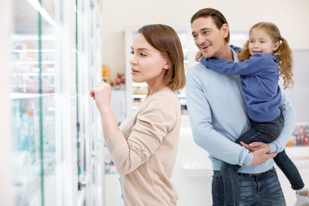 Family in drugstore. Pleasant nice woman choosing product while man holding girl