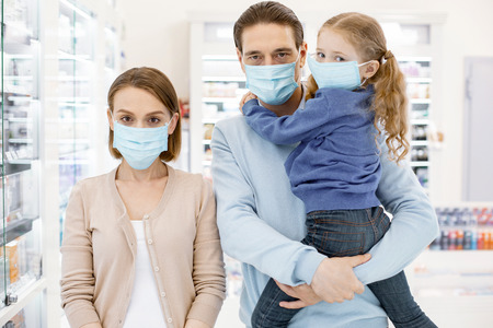 Season cold. Concentrated sad family wearing mask and looking at camera