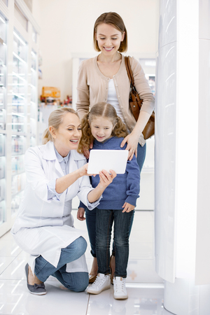 Fun in drugstore. Cheerful female pharmacist talking to family while using tablet