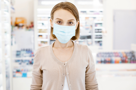 Severe cold. Worried tired woman posing in drugstore and looking at camera