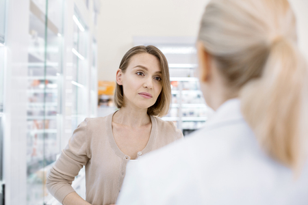 Health issue. Dismal dolorous woman posing on blurred background while communicating with female pharmacist