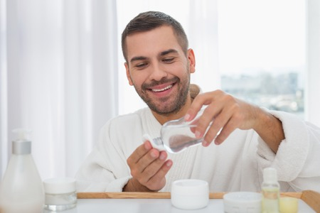 Skin cleansing. Positive nice man using a skin lotion while cleansing his skin Stock Photo