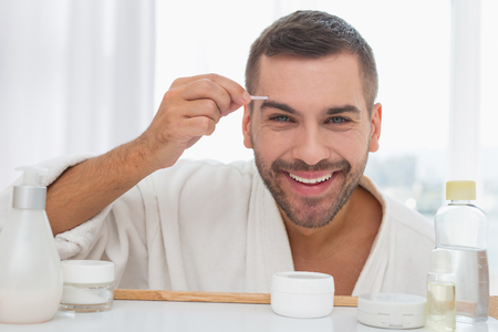 My look. Cheerful delighted man looking into the bathroom mirror while using eyebrow tweezers Stock fotó