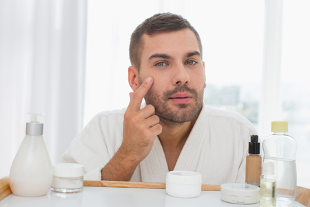 Perfect skin. Attractive young man looking at his face while applying cream