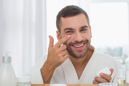 Positive mood. Delighted cheerful man smiling while applying facial cream Stock Photo