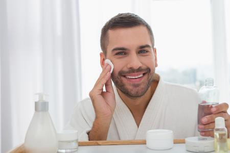 Positive mood. Joyful happy man smiling while cleaning his face