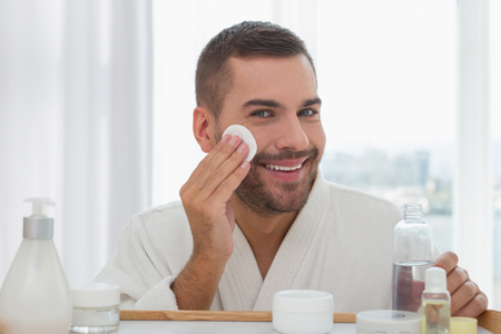 Great mood. Cheerful nice man smiling to you while cleaning his skin