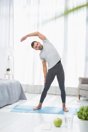 Körperbewegungen. Hübscher netter Mann, der eine körperliche Übung während des Turnens tut