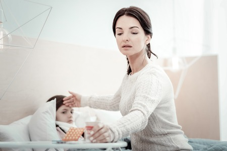 It is for you. Serious female person stretching arm while taking medicine and sitting near her daughter