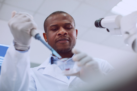 My inspiration. Concentrated skilled scientist conducting a blood test and wearing a uniform