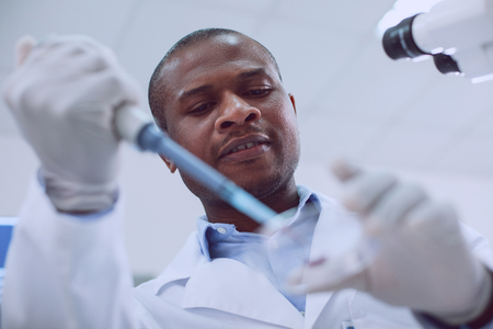 Being a biologist. Inspired skilled scientist conducting a blood test and wearing a uniform Stock Photo