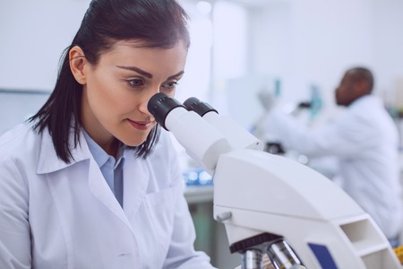 I feel happy. Content smart scientist working with her microscope and wearing a uniform Banco de Imagens