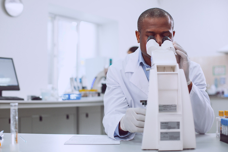Best work ever. Smart experienced researcher working on his microscope while working in the lab