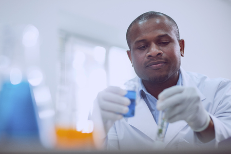 Interesting task. Delighted afro-american scientist doing a test while working in the lab